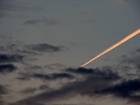 夕空の飛行機の反射光