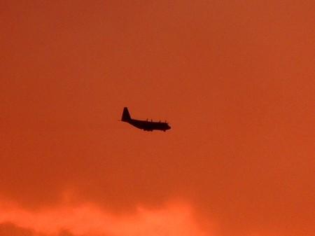 夕焼けの中を飛ぶ空自輸送機