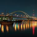 写真: 都会の運河を見下ろすアーチと妖光